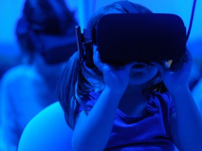 Showcases a virtual reality headset. This is a main focus of the article.